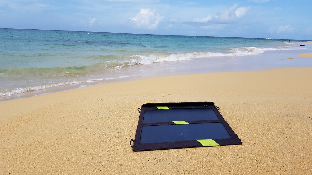 sitting by the beach working using Xdragon solar cellphone charger remote worker working on cellphones