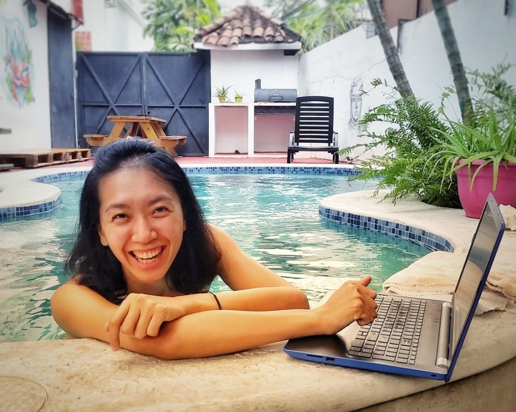 digital nomad working on a laptop in a swimming pool Casa Areka hostel