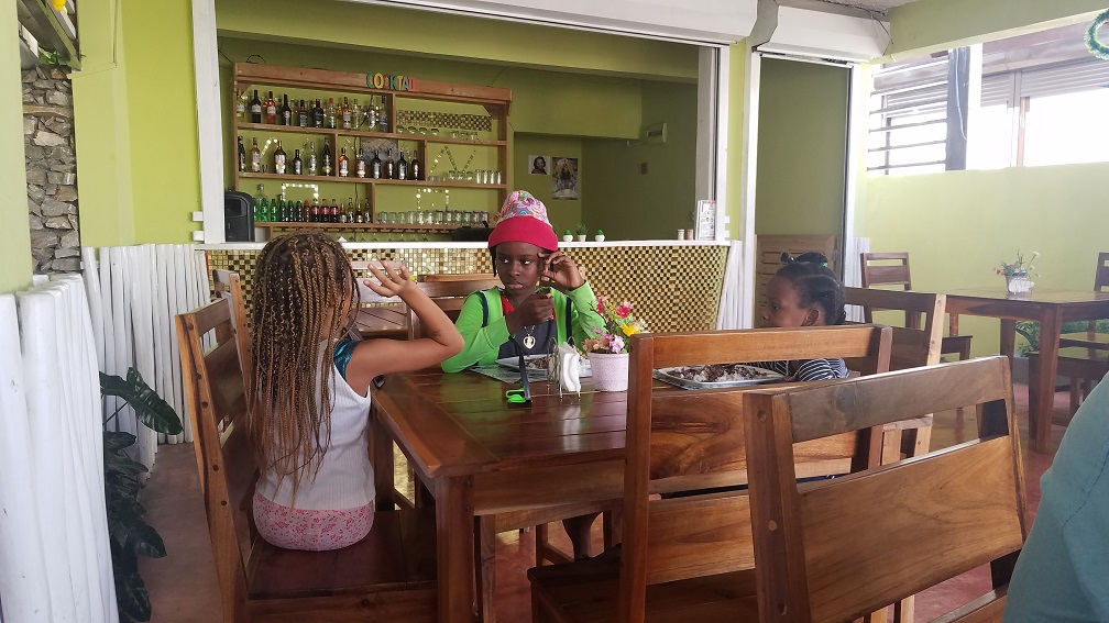 three local dominican-Haitian kids eating lunch together Las Terrenas